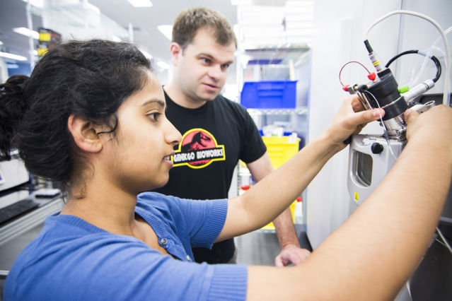 Ginkgo Bioworks staff members Ramya Prathuri (left) and Nate Tedford work at the mass spectrometer in the Ginkgo foundry.