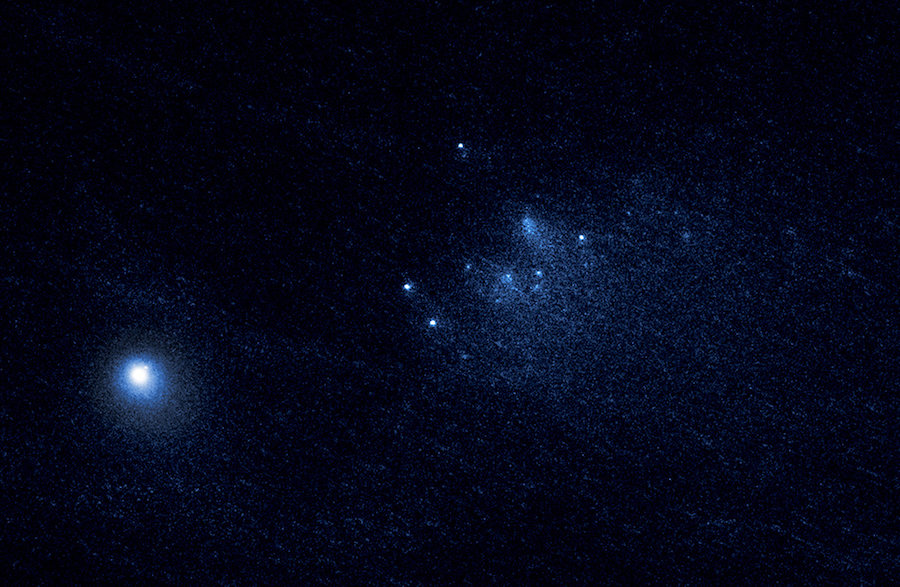 The comet breaks apart: This NASA Hubble Space Telescope image reveals the ancient comet 332P/Ikeya-Murakami disintegrating as it approaches the sun. The observations represent one of the sharpest views of an icy comet breaking apart. The comet debris consists of a cluster of building-size chunks near the center of the image. They form a 3,000-mile-long trail, larger than the width of the continental U.S. The fragments are drifting away from the comet, dubbed comet 332P, at a leisurely pace, roughly the walking speed of an adult. Credit: NASA, ESA and David Jewitt/UCLA