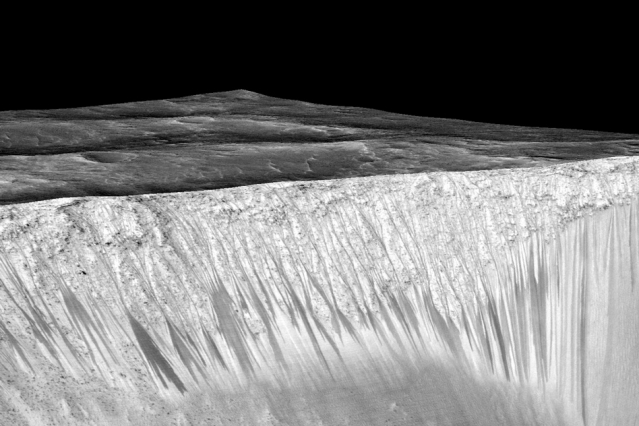 Mars' Valles Marineris canyon, pictured, spans as much as 600 kilometers across and delves as much as 8 kilometers deep. The image was created from over 100 images of Mars taken by Viking Orbiters in the 1970s. Photo Credits: NASA